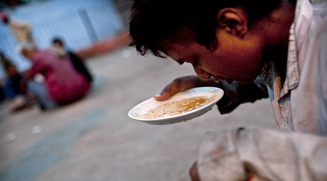 MDG : Human rights and food security : A Indian youth eats food distributed by local charity, India